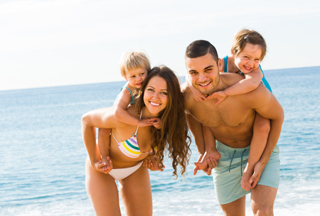 Happy young family of four in vacation at sea shore