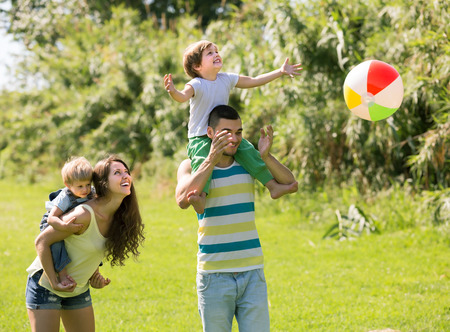 Happy smiling parents with little daughters playing together outdoor photo