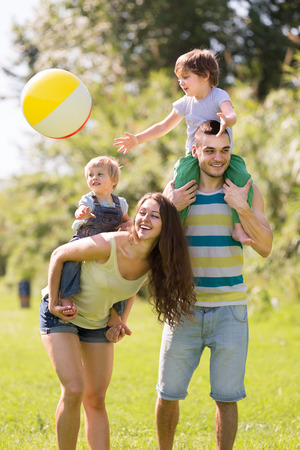 Happy husband, wife and their children playing ball summer day photo