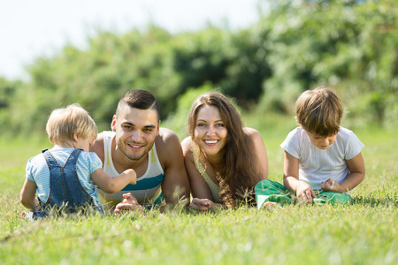 3 4 years: Portrait of happy smiling young parents with children in grass at park. Focus on man Stock Photo