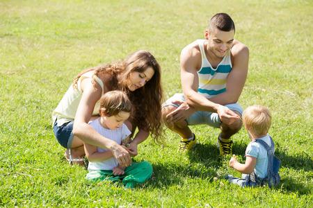 2 to 3 years: Felice giovane famiglia con due piccole figlie in parco estivo. Concentrarsi sulla donna Archivio Fotografico