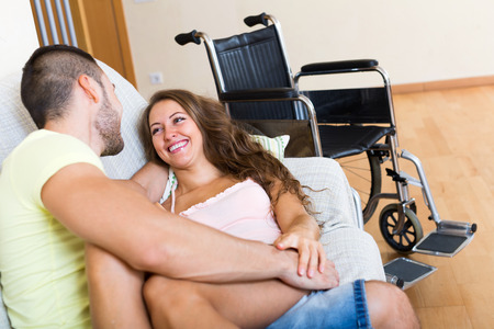 sex tenderness: Romantic relationships between young people and invalid chair at background Stock Photo
