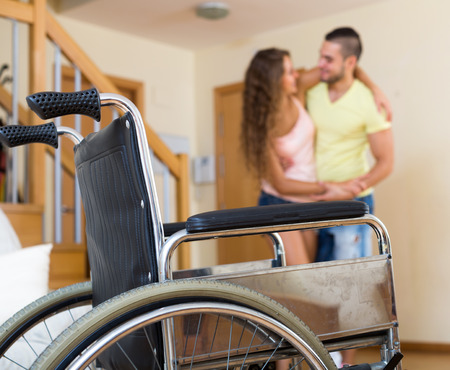 invalidity: Male social worker assisting girl during rehabilitational  period at home. Focus on wheelchair