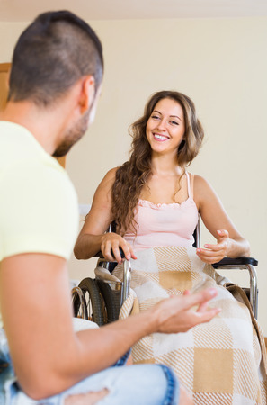 invalidity: Handsome man and his handicapped girl in wheelchair having conversation