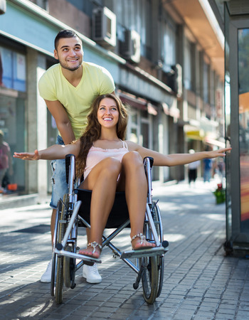 the spouse: Husband taking smiling spouse on wheelchair in playful mood outside Stock Photo