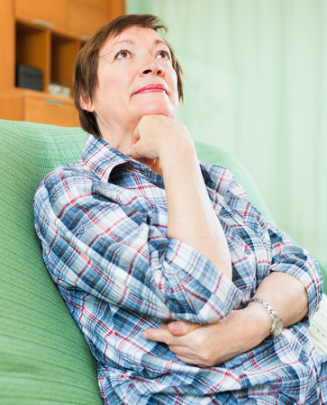 Thoughtful mature woman with sad face and in casual clothes laying photo