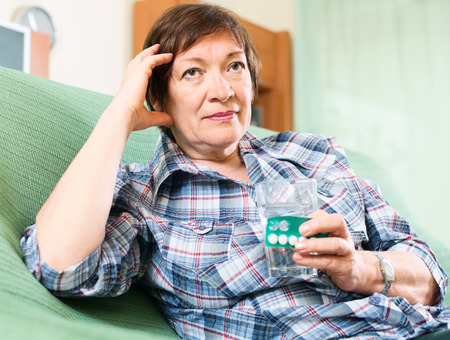 female pensioner with pills and glass of water indoor photo