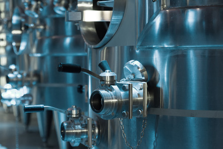 stell: Closeup of equipment of contemporary winery with  stell barrels. Focus on valve of pipes