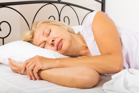 Blonde mature woman in pajamas sleeping with white pillow in bed at home photo