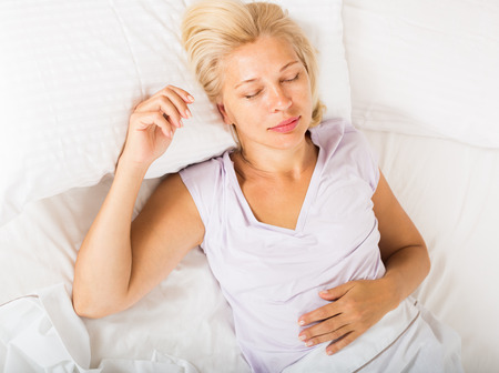 Middle-aged blonde woman sleeping on white pillow in bed at home photo