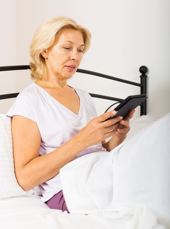 mature woman with eBook laying in  bed at home photo