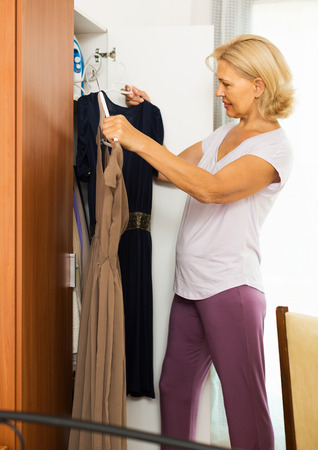 get dressed: Mature woman at wardrobe. She thinking what get dressed