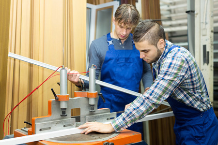 skilled operator: A couple of workers toil around the milling machine