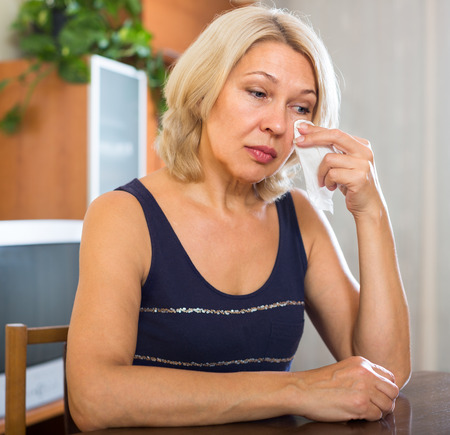 sobbing: Sad mature  woman sitting on chair  in home