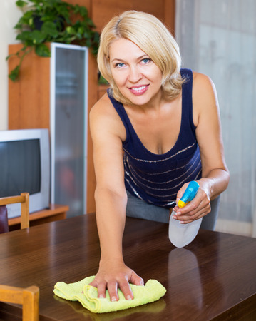 cleanser: Mature housewife cleaning table with cleanser and rag in living room at home Stock Photo