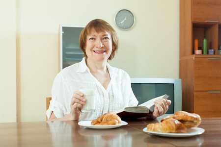 Positive elderly woman having breakfast with book and milk in morning photo