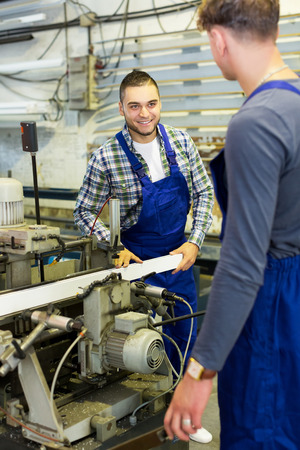 skilled operator: Two  males do his job on a machine in factory Stock Photo