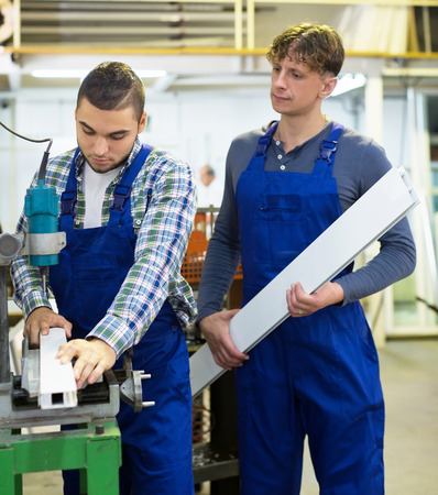 toolroom: Two careful young men working on a machine in toolroom Stock Photo