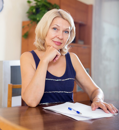 parsimony: Happy mature woman signing documents at table