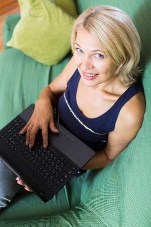 netbook: mature woman with netbook sitting and resting on sofa in living room