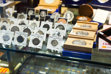 numismatics: BARCELONA, SPAIN - OCTOBER 28, 2014: Many gold and silver coins on counter at numismatics store