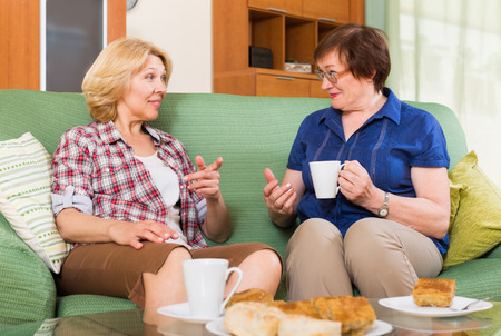 talkative: Two positive mature women drinking tea and gossiping at home