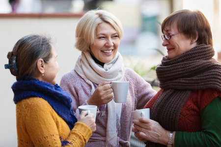 Smiling mature female in warm clothes having cup of hot tea on terrace 스톡 콘텐츠
