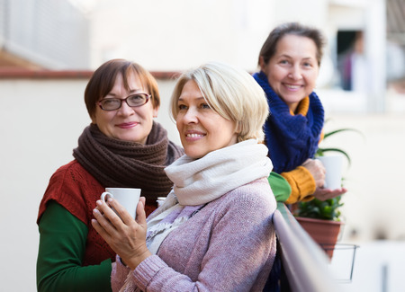 morning coffee: Positive smiling elderly female friends drinking coffee at patio. Focus on blonde