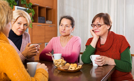 sad senior female friends drinking coffee and sharing problems at table
