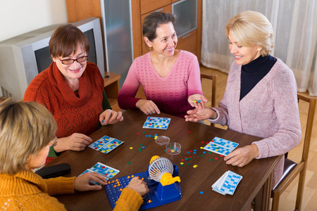 Positive senior female friends sitting at desk with bingo