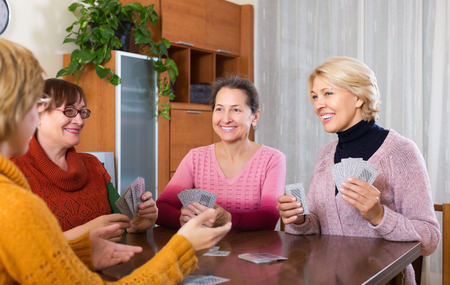 Mature women having fun with pack of cards indoor photo