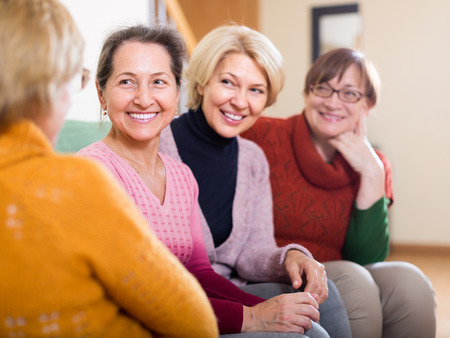 Portrait of senior women having discussion indoor and laughing. Focus on one