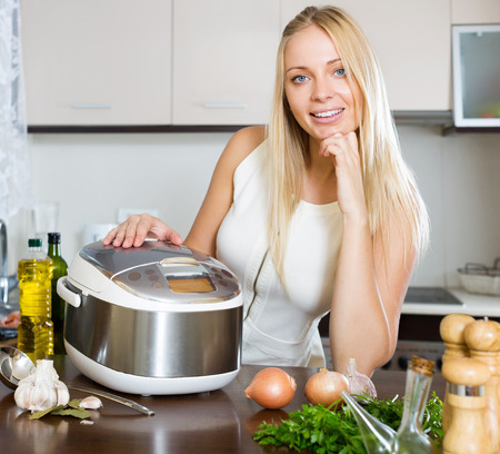 Happy young woman using new  slo-cooker in kitchen photo