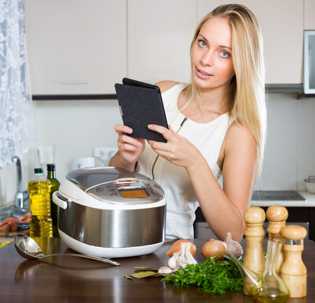 ereader: Blonde woman reading ereader while with new electric multicooker doing food at home Stock Photo
