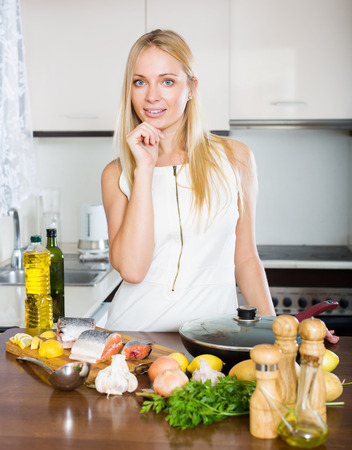 Smiling young woman using new slow-cooker in kitchen photo