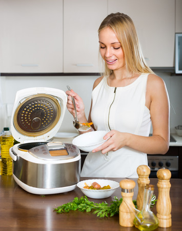 Smiling blonde housewife cooking with new electric multicooker at home photo