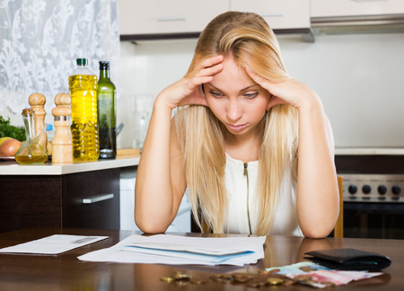utility payments: Young sad blonde housewife filling in utility payments bills at home Stock Photo