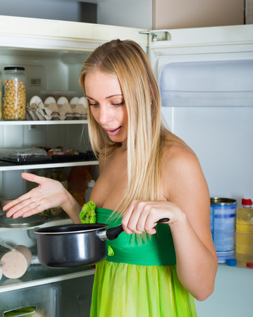 frowy: Young blonde housewife holding foul food near refrigerator at home