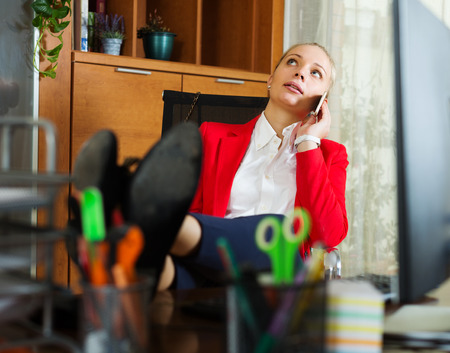 tedious: Young woman having a tedious time and speaking by mobile  at office
