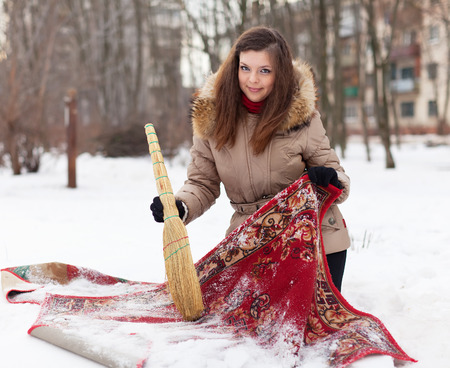topcoat: Smiling woman cleans red carpet with snow in winter day outdoor