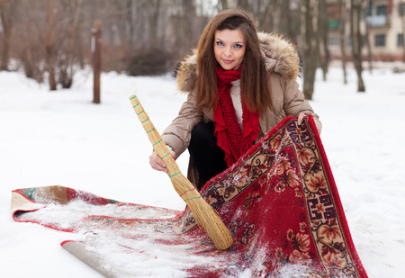 topcoat: Young woman cleans rug with snow in winter outdoor