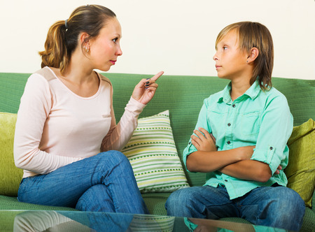 Mature mother berating teenager son in living room at home photo