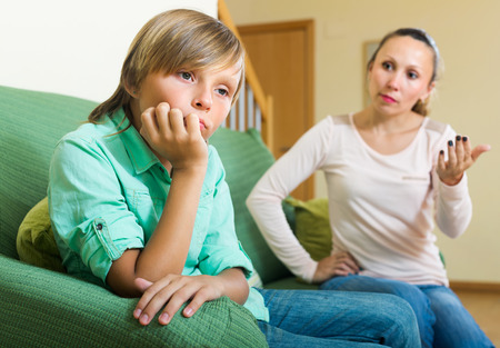Angry mother scolding naughty teenage son in home interior. Focus on boy photo