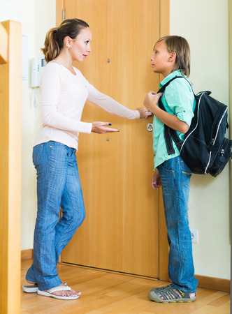 lecturing: Positive mature woman lecturing boy before he goes to school