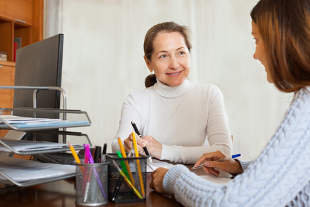 Mature smiling woman talking with employee with laptop at office