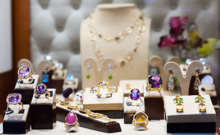 14k: Golden jewelry with gems at showcase of jewelry shop