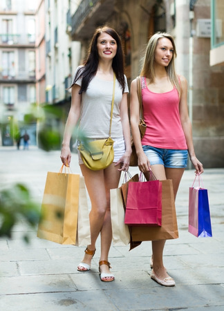 Beautiful smiling blonde and brunette with shopping bags walking by street photo