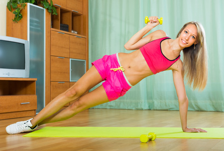 girl working out: Active happy girl working out on exercise mat at home