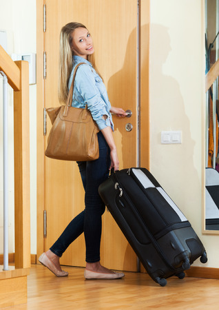 interphone: Woman with luggage staying near door Stock Photo