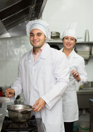 Two smiling head-cooks cooking at professional kitchen in the cafe. Focus on man photo